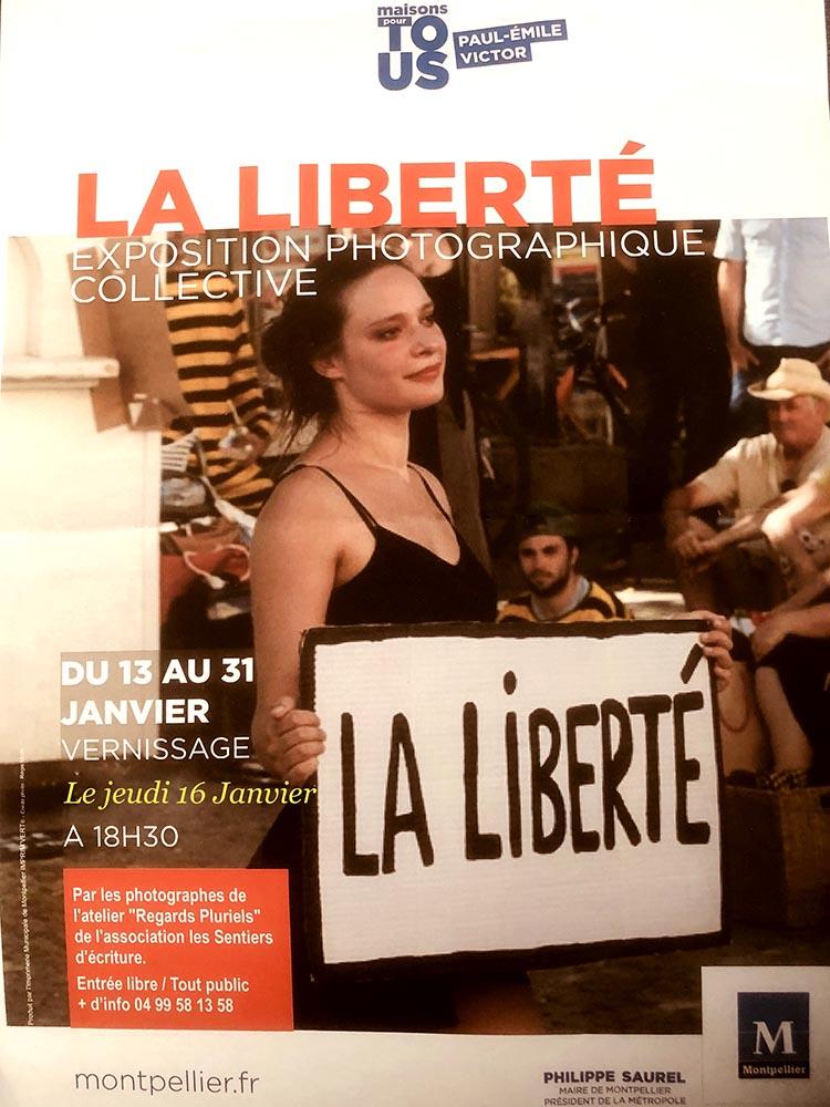 """Affiche expo photo sur la liberté - Une fille qui tiens une pancarte avec les mots """"La liberté"""" écrit dessus."""
